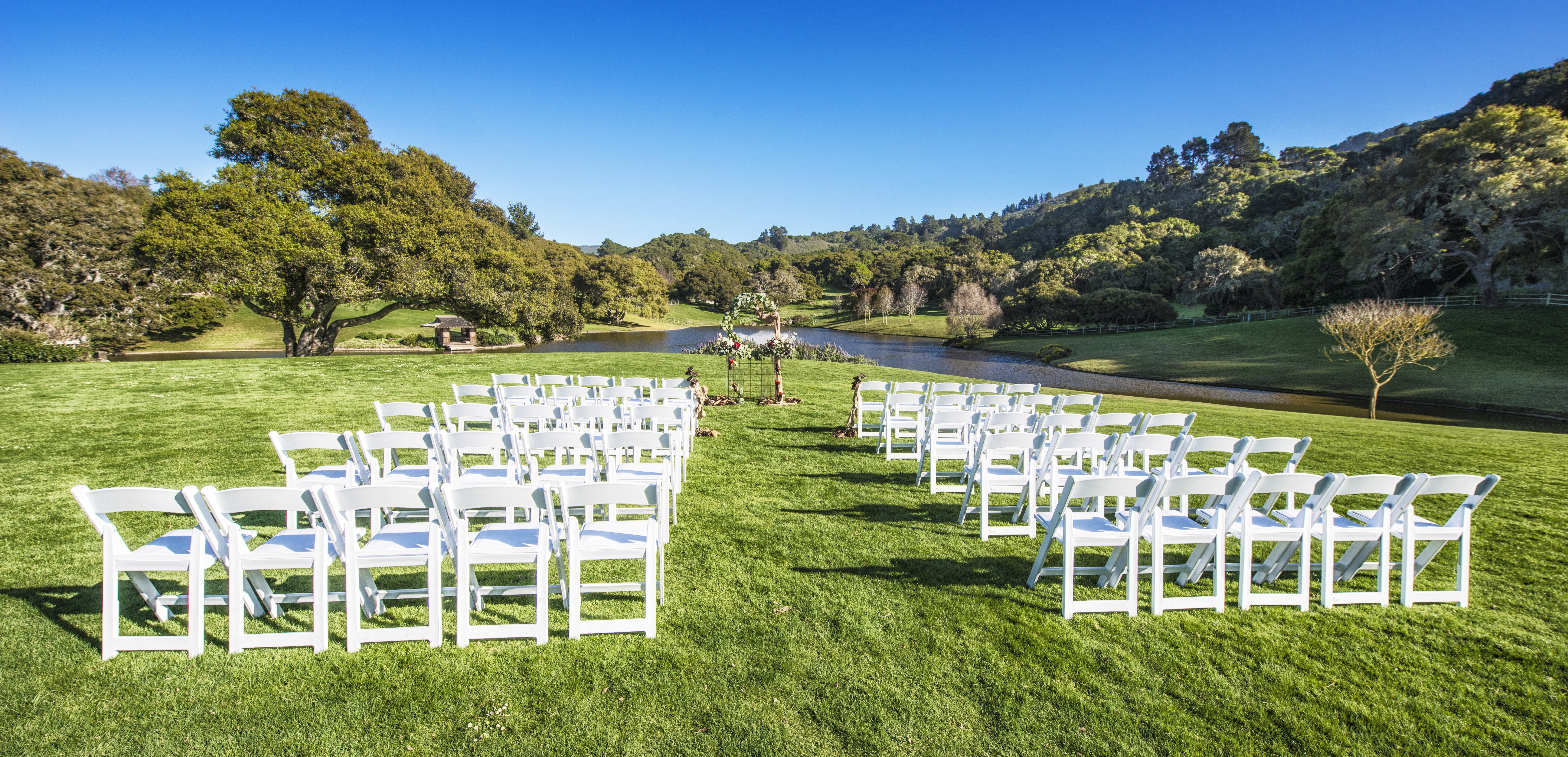 Quail Meadows outdoor ceremony set-up with chairs and view of pond