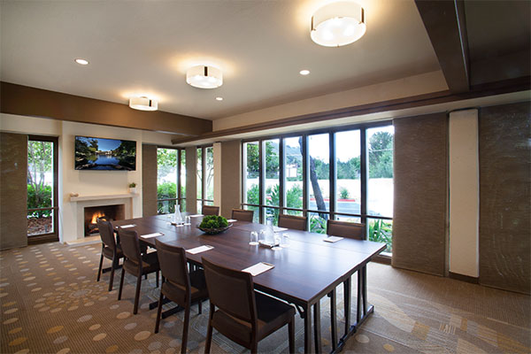 Glass House board room style with TV monitor, fireplace and views of grounds